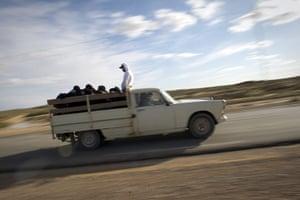 Libya unrest: Tunisians in Libya travel by pickup truck, en route to the Ras Jdir border