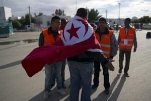 Libya unrest: A Tunisian volunteer prepares to welcome compatriots at the Rad Jdir border
