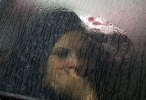 Libya unrest: A Tunisian woman is seen through the window of her husband's car