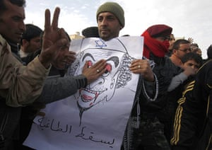 Libya unrest: A protester holds a drawing depicting Muammar Gaddafi in Tobruk City