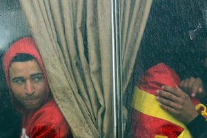 Libya unrest: A man who recently fled Libya sits on a bus with other displaced people