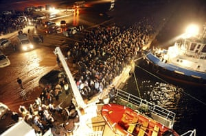 Libya unrest: People wait to board a Turkish ferry at the port of Benghazi