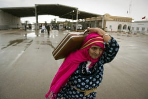 Libya unrest: A Tunisian woman carries her bags past the Rad Jdir border post