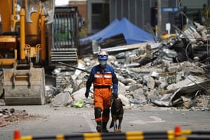Christchurch earthquake: A Japanese rescue worker and dog walks past the rubble of the CTV building