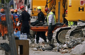 Christchurch earthquake: Emergency services remove a body from the destroyed CTV building