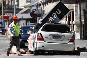 Christchurch earthquake: A rescue worker walks in front of a damaged car in Cathedral Square