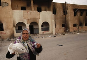 libya: Woman walks past a burnt state security building in Tobruk, Libya