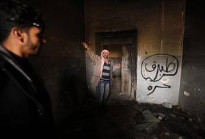 libya: Man gestures inside a burnt state security building in Tobruk east of Libya