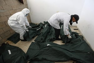 libya: Mortuary assisstants  look at unidentified burned corpses