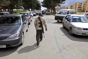 libya : A man walks with a rifle in Shahat