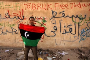 libya unrest: A Libyan anti-government protester holds a flag in tobruk