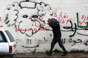 libya unrest: An anti-government demonstrator passes by graffiti in Benghazi
