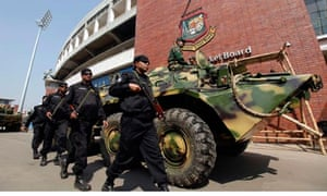 Members of Rapid Action Battalion (RAB) march past an Armoured Personnel Carrier in Dhaka