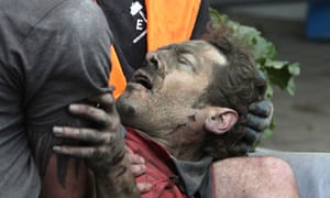 A man is seen after being pulled from the rubble after an earthquake in Christchurch
