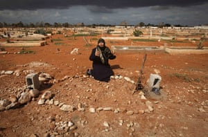 Libya 26 Feb: The mother of a Libyan killed in the recent clashes sits next to his grave