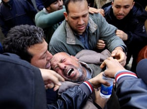 Libya 26 Feb: A Libyan mourner collapses during a funeral