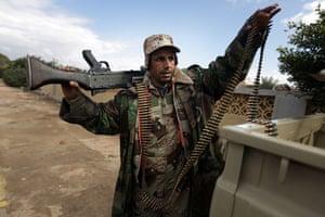 Libya 26 Feb: A Libyan army paratrooper, who defected, loads a machine gun