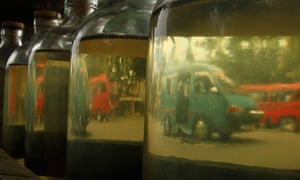 Cars are reflected on bottles of petrol as they are sold in Indonesia