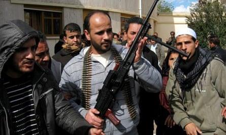 Libyan civilians display a machine gun they claim to have taken from mercenaries