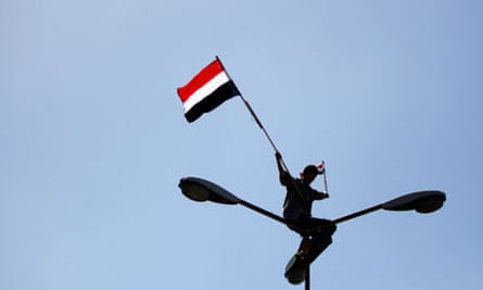 An anti-government protester waves the Yemeni flag from the top of a lamppost in Sana'a