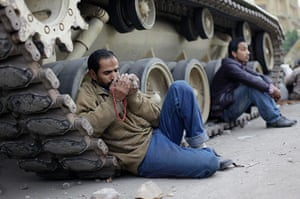 Egypt 05/02: A protestor prays as he leans on a military tank in Tahrir Square, Cairo
