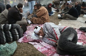 Egypt 05/02: An injured anti-government protester sleeps in Tahrir Square