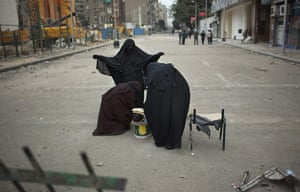 Egypt 05/02: Women protesters search a woman in a checkpoint outside Tahrir square