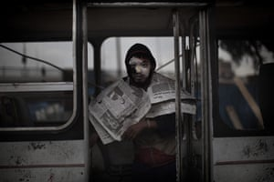 Egypt protests day 13: An anti-government protester stands inside a destroyed bus
