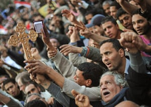 Egypt protests day 13: Coptic Christians raise a cross as they pray amongst protesters