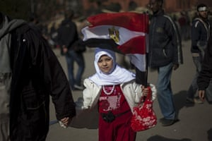 Egypt protests day 13: A girl holds an Egyptian flag as she joins an anti-Mubarak demonstration