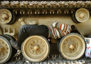 Egypt protests day 13: A protester sleeps on the track wheels of a tank