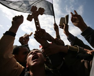 Egypt protests day 13: Protesters hold a Christian coptic cross and copies of the Qur'an