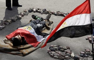 Egypt protests day 13: An opposition supporter plays the role of a victim