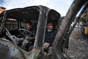 Egypt protests day 13: Egyptian anti-government demonstrators sit in a burned police vehicle