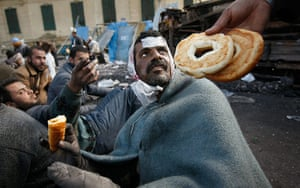 Egypt protests day 13: Food is offered to a wounded anti-government protester