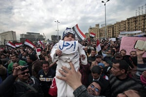 Egypt protests day 13: An anti-government demonstrator holds a baby wearing a hat saying 'Leave'