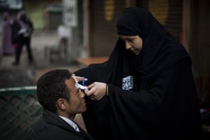 Egypt protests day 13: An anti-Mubarak protester receives care from a volunteer nurse