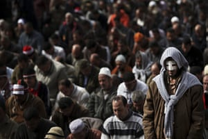 Egypt protests day 13: An injured anti-government protester prays with other Egyptians