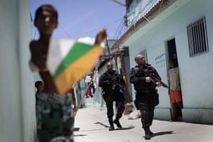 24 hours: Rio de Janeiro, Brazil: A boy plays with a kite as police officers patrol