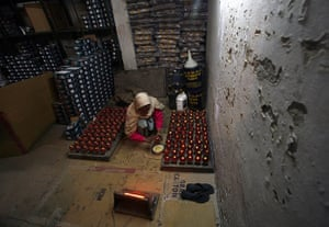 24 hours: Meerut, India: A worker shines cricket balls before packing them