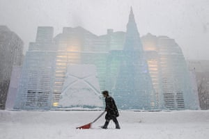24 hours: Sapporo, Japan: A man ploughs snow in front of an ice sculpture