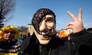 A protester wears a mask of Silvio Berlusconi draped with a pair of knickers