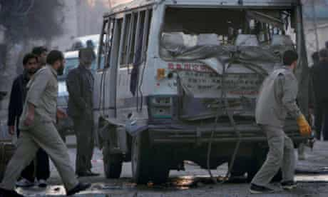 Afghans walk past a bus damaged by a bomb in Jalalabad, eastern Afghanistan