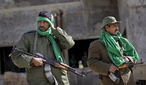 Libya: Pro-Gaddafi security forces stand near a checkpoint in Qasr Banashir