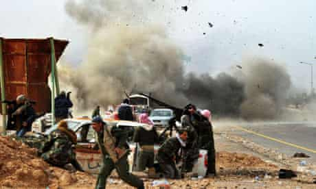 A Libyan army tank shell bursts among rebel fighters near the oil town of Ras Lanuf.