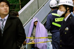 Japan earthquake: A man sits wrapped in a blanket after he was evacuated, Japan