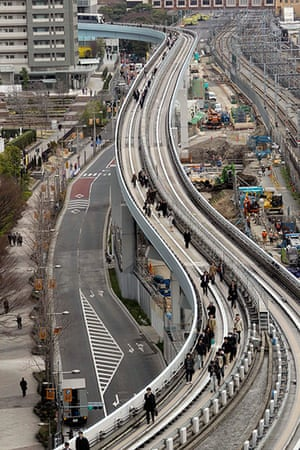 Japan earthquake: Yurikamome train passengers walk on the elevated track in Tokyo, Japan