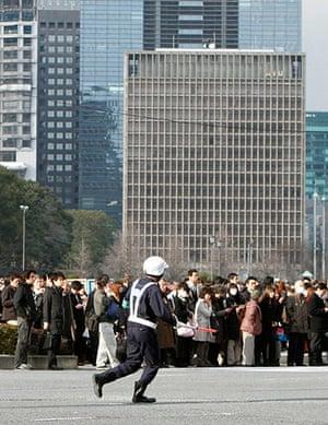 Japan earthquake: A policeman runs across a street after evacuating buildings in Tokyo, Japan