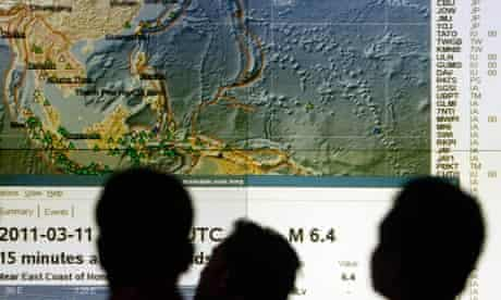 Officials at the Indonesian tsunami early warning centre watch as waves fan out from Japan