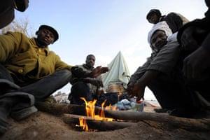 Ras Jdir Refugees: Malian refugees warm their hands with a fire